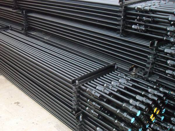 Several pallets of hollow sucker rod are placed in the warehouse.